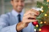 Close up of businessman hand decorating christmas tree in modern office. Business man decorating xma poster