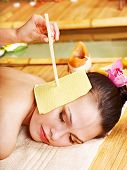 foto of ear candle  - Woman getting massage with ear candle in bamboo spa - JPG