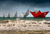 Rescue And Leadership Concept, A Red Paper Boat Of The Coast Guard Rescues Four White Boats That Are poster