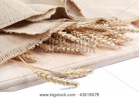 Ears Of Wheat Under The Canvas On A Wooden Board.