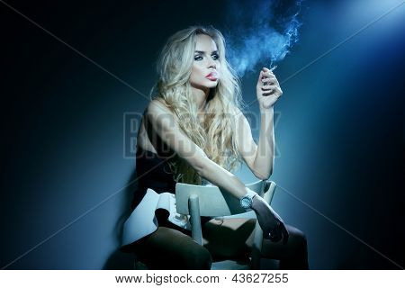 Elegant Blonde Girl Sitting On Chair, Smoking Cigarette, Thinking.