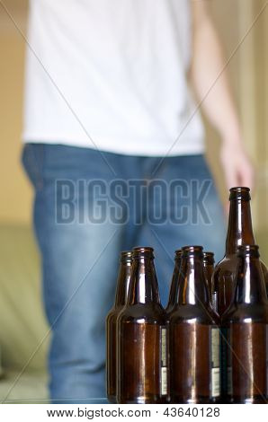 Man standing near a table full of empty beer bottles