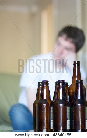 Vertical, man looking to left with empty beer bottles