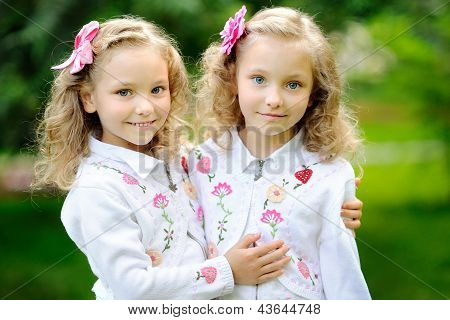Portrait Of Two Sisters Twins In The Summer