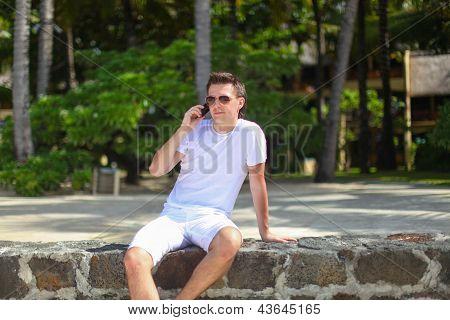 Joven hablando por teléfono de vacaciones