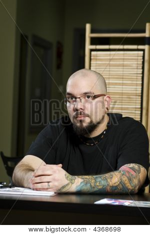 Owner Of Tattoo Parlour Sitting At Desk