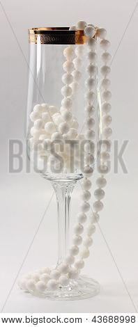 Transparent Tall Glass And White Necklace On A White Background