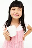 stock photo of mug shot  - Beautiful little asian girl with mug isolated on white background - JPG
