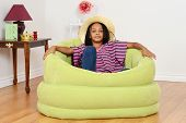 stock photo of cornrow  - black child relaxing in green chair in living room - JPG