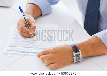 business, tax, office, school and education concept - man filling a form