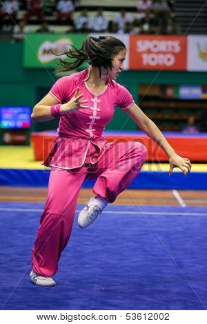 KUALA LUMPUR - NOV 03: Elizabeth Lim of Australia shows her fighting style in the 'Nan quan compulsory' event at the 12th World Wushu Championship on November 03, 2013 in Kuala Lumpur, Malaysia.