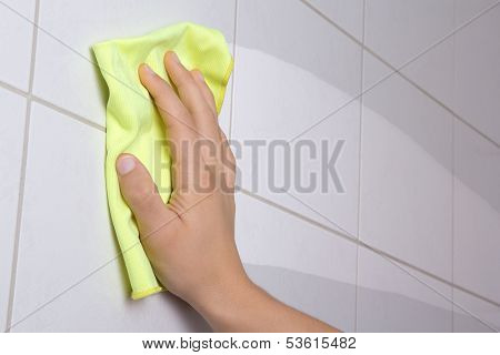 Hand With Yellow Rag Cleaning The Bathroom Tiles