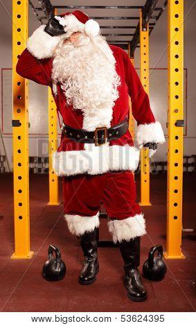 Sweating, tired Santa Claus having break in training in gym