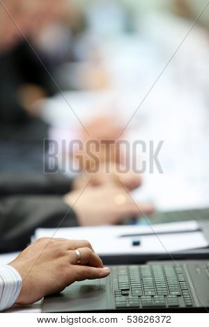 Photo of male's hands on laptop during business conference. Shallow depth of field