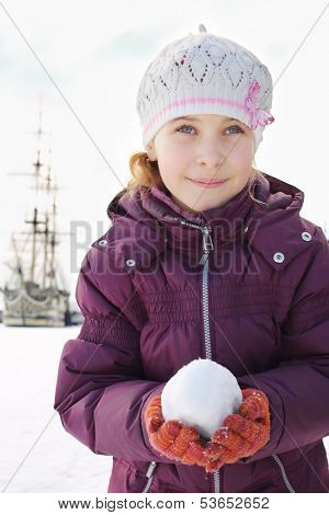 The girl in a cap and gloves holding snowball next to a sailboat
