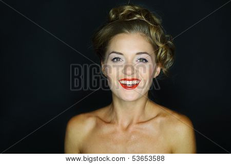 Portrait of a laughing woman with eyes wide open on a dark background