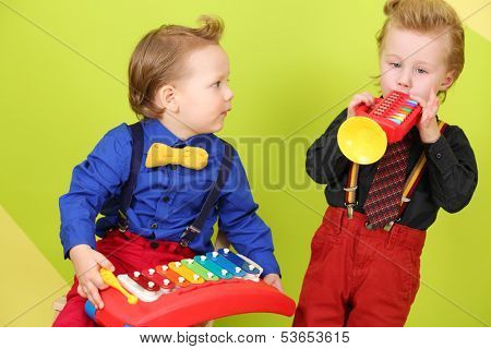 Two little boys in bright clothes with children musical instruments: trumpet and metallophone