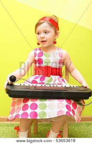 Mod little girl in a bright dress holding on her lap toy piano and microphone