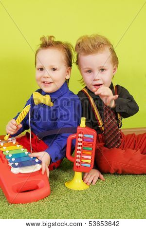 Two boys are sitting back to back with children trumpet and metallophone