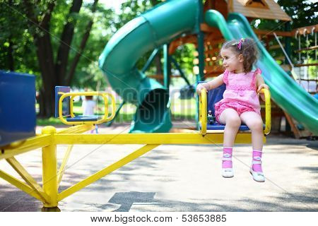 Little girl in a pink dress on the carousel spins on the playground