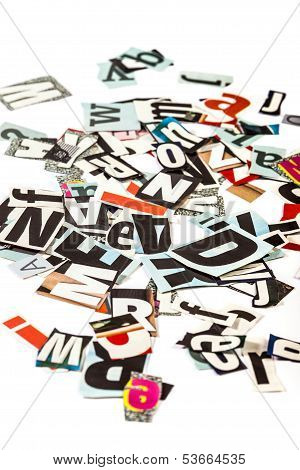 Scattered cut out letters on white background