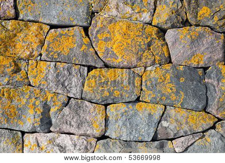 Background Texture Of Old Stone Wall With Bright Lichen