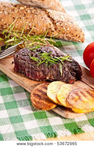 Grilled Beef Steak, Baked Potatoes And Vegetable On Wooden Breadboard