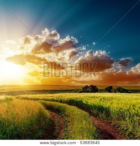 dramatic sunset over road in fields