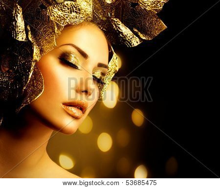 Fashion Glamour Makeup. Beauty Model Girl with Glamor Golden Make-up and Hairstyle. Holiday Gold Makeup and Hair with Floral Design over Black Background