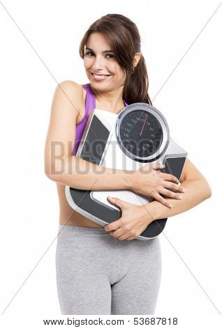 Beautiful athletic woman smilling and holding a scale, isolated on white