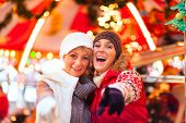 picture of merry-go-round  - Two women or friends during advent season or holiday in front of a carousel or merry - JPG