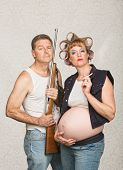 stock photo of hillbilly  - Negligent pregnant hillbilly couple with rifle and cigarettes - JPG
