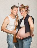 stock photo of hillbilly  - Hillbilly with rifle and adoring pregnant wife - JPG