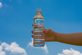 picture of bottle water  - teen girl holding a water bottle up with a blue cloudy sky - JPG