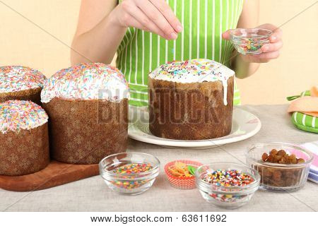 Woman decorating Easter cake, close up