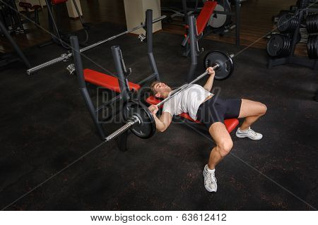 handsome young man doing bench press workout in gym
