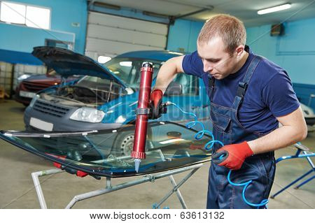 Automobile glazier adding glue on windscreen or windshield of a car in auto service station garage before installation