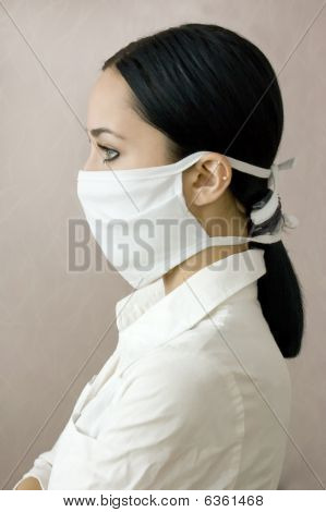 The beautiful young girl in a medical mask