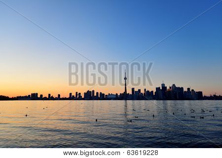 Toronto sunset silhouette at dusk over lake with urban architecture.