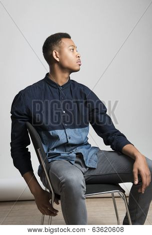 Profile portrait of handsome dark skinned male model sitting and wearing casual clothes against white background