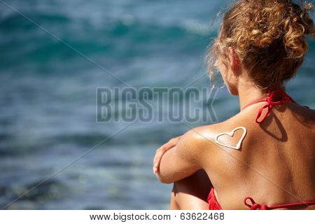 teenage girls back with sunburn and heart of sun lotion