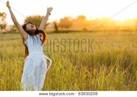 Joyful woman wearing white dress in a rice field after harvest, Thailand