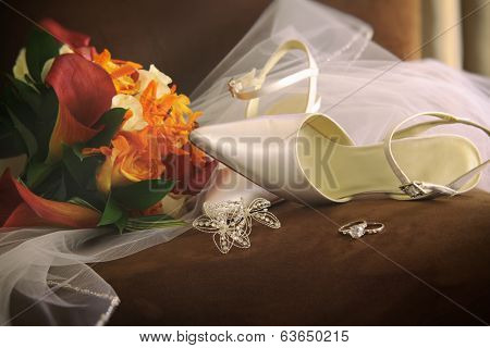 Wedding shoes with veil and rings on chair