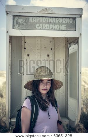 Female Teenager With Straw Hat In An Old Call Box