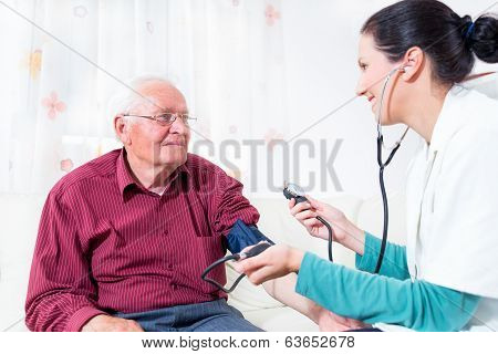 Young Doctor Measuring Blood Pressure Of Senior Patient