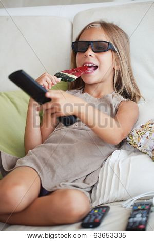 7 years old child watching tv sitting on sofa at home