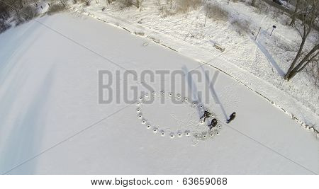 Aerial view to fishermen are drilled holes in the ice river to catch fish