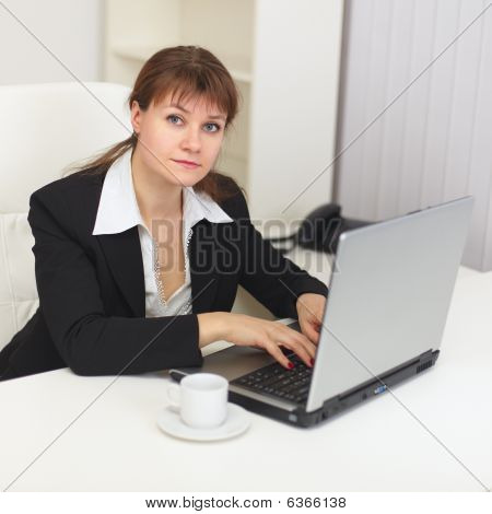 Young Beautiful Woman With Laptop Sits At A Table