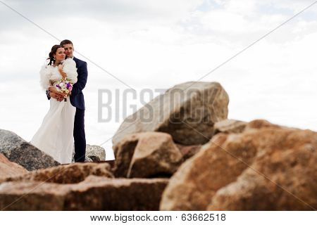 Happy newlyweds standing among the rocks on the beach.