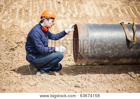 Man examining a pipe in a construction site